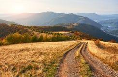 Väg i bergen Underbart höstberglandskap majestätiska mulna moln i solljus prydlig skog på arkivbilder
