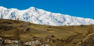 Väg i de höga snö-korkade bergen _ arkivfoton