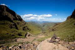 Väg i den gröna dalen mellan två berg Arkivbilder
