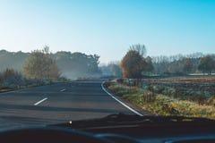 Väg i det dimmiga lantliga landskapet som ses från vindrutan av bilen Fotografering för Bildbyråer