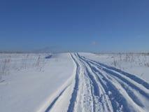 Väg i det snöig fältet arkivfoton