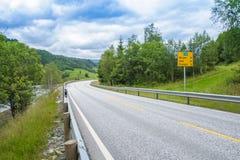 Väg i Norge längs skogen och floden Arkivfoto
