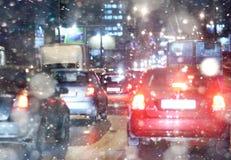 Väg i vinternatten, trafikstockningar, snöstad Arkivbild