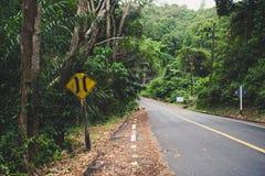 Väg igenom i skogen med den gamla guideposten Royaltyfri Bild
