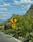 Väg 15 mph teckenvarning av kurvor i vägen framåt Arkivbilder