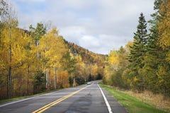 Väg nära den norr kusten av Minnesota med träd i nedgångfärg Arkivbild