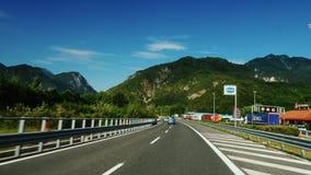Väg nära Graz, Österrike, Juni 2017: Den storartade huvudvägen i Österrike, i de härliga fjällängarna för bakgrund Snabbt ritt stock video