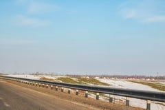 Väg och fält med smältande snö, soligt landskap arkivbild