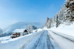 Väg och hus för morgonvinter dimmig lantlig alpin Arkivbilder