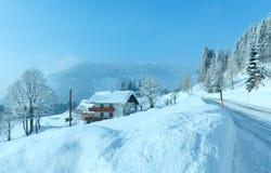Väg och hus för morgonvinter dimmig lantlig alpin Royaltyfri Foto