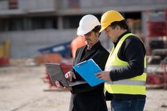 Väg-och vattenbyggnadsingenjör som ger anvisningar till byggnadsarbetaren arkivbild
