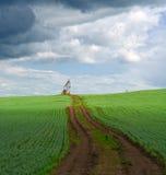 Väg på ett grönt fält som leder till en stråle som pumpar enheten för att pumpa olja Arkivbild