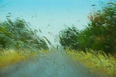 Väg som ses till och med den våta bilvindrutan Royaltyfri Bild