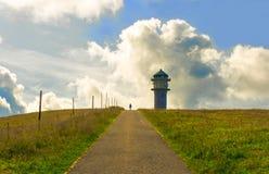 Väg till ett torn i det gröna gräset och molnen på berget Royaltyfria Foton