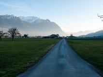 Väg till och med äng in mot berg Arkivfoton