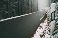 Väg till och med den Odenwald skogen i vinter Arkivfoton