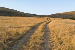 Väg till och med fältet och kullarna Royaltyfria Foton