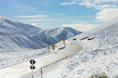 Väg till och med snöig berg. Arkivfoto