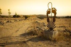 Väg till Santiago - rostig metallisk struktur med en gå pinne, fot och ett skal arkivfoto
