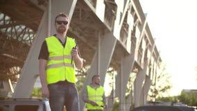 Vägarbetare med trafikstången som isoleras, och walkietalkiearbete på testpunktavgiftvägar stock video