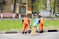 Vägarbetare på en stadsgata målar en trottoarkant Royaltyfria Foton