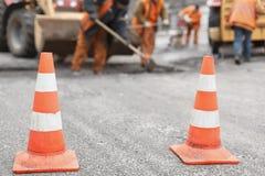 Vägarbetare reparerar vägen, kottar i förgrund royaltyfria bilder