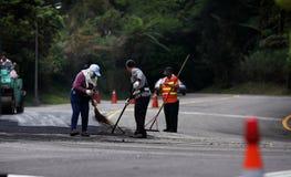 Vägarbetare som lägger asfalt Arkivbild