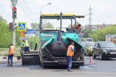 Vägarbeten på asfaltstenläggning i Omsk Arkivbild