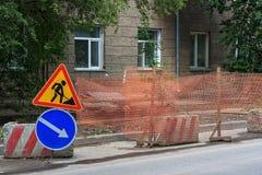 Vägarbeten på stadsgatan Tecken för vägarbete och omväg arkivfoton
