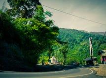 Vägasfaltkurva med den gröna skogen på sidoberget i puncak bogor royaltyfri fotografi