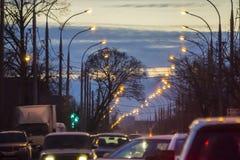 Vägbro med ljusen och den rörande bilen i dimman efter regn arkivbilder