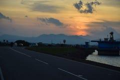 Vägen, floden, bergen och den härliga solnedgången royaltyfria foton