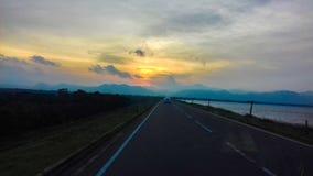 Vägen, floden, bergen, träden och den härliga solnedgången arkivbild
