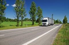 Vägen fodrade med poppelgränden i bygden, övergående vit lastbil Royaltyfri Bild