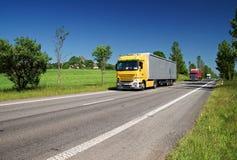 Vägen fodrade med träd i ett lantligt landskap, tre passera färgade lastbilar Royaltyfri Bild