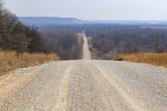 Vägen går på för evigt - grusväg i vinterelasticiteter över kullar nästan till den disiga horisonten royaltyfria bilder