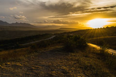 Vägen i bergen på solnedgången Arkivfoton