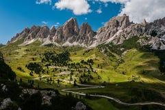 Vägen med många vänder att leda till och med bergmassiverna i de alpina dolomitesna Royaltyfri Bild