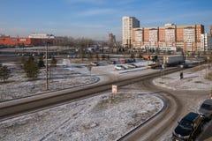 Vägen med parkering och en offentlig trädgård på bakgrunden av bostads- hus i vinter Royaltyfri Foto