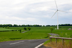 Vägen mellan fälten med väderkvarnar royaltyfria foton