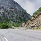 Vägen nära den farliga smula lutningen och varningstecknet Royaltyfri Foto