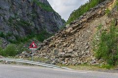 Vägen nära den farliga smula lutningen och varningstecknet Arkivfoton