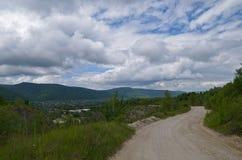 Vägen ner till byn och bergskedjan i distaen Arkivfoto