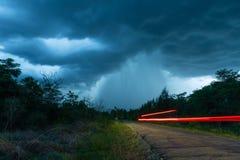 Vägen som det leder till det fallande regnet från det tjocka molnet royaltyfria foton
