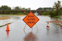 Vägen som framåt stängs, undertecknar över den regn översvämmade gatan Arkivbild
