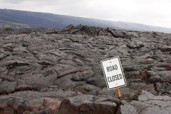 Vägen stängde sig undertecknar in mitt av ett lavaflöde Arkivfoto