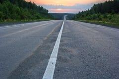 Vägen sträcker av in i solnedgången Arkivbild