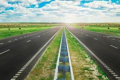 Vägen sträcker in i avstånd Fält med baler av hö och i mitt av spåret Royaltyfri Bild