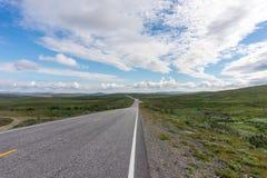 Vägen sträcker in i avståndet på en bakgrund av gröna ängar Fotografering för Bildbyråer