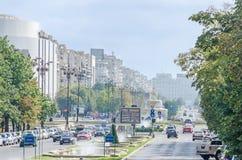 Vägen till fyrkanten Piata Unirii med shoppar, trafikbilar, turister och utomhus- springbrunnar bucharest romania Arkivfoto